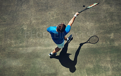 Buy stock photo High angle shot of a focused young man playing tennis outside on a tennis court during the day