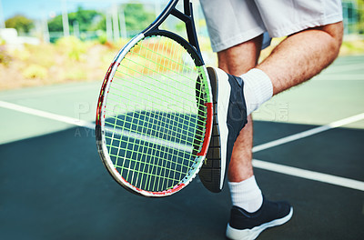 Buy stock photo Cropped shot of an unrecognizable male tennis player kicking his tennis racket outdoors on a tennis court