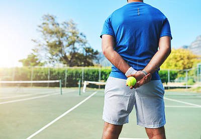 Buy stock photo Rearview shot of an unrecognizable male tennis player holding a tennis ball on a court outdoors