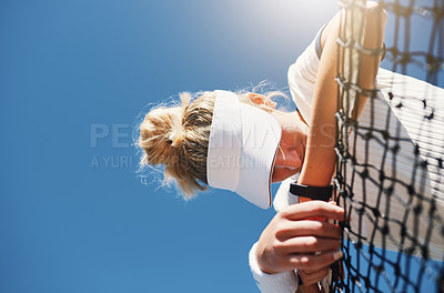 Buy stock photo Cropped shot of a young female tennis player feeling tired and slouching over the net on a tennis court outdoors