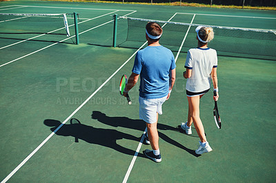 Buy stock photo Full length shot of two young tennis players talking while walking together outdoors on a tennis court