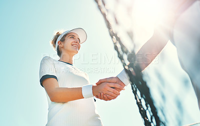 Buy stock photo Cropped shot of an attractive young female tennis player shaking hands with an opponent outdoors on the court