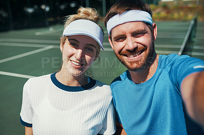 Buy stock photo Portrait of a happy young couple taking selfies while playing tennis together outdoors on the court