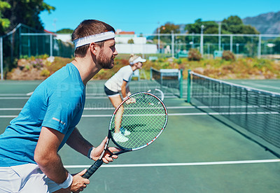 Buy stock photo Cropped shot of a handsome young male tennis player playing together with a female teammate outdoors on a court