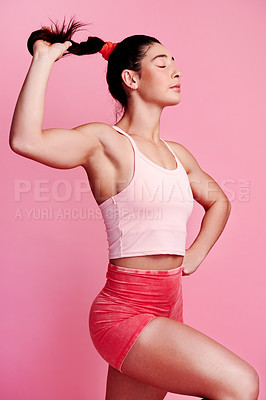Buy stock photo Studio shot of a sporty young woman holding her ponytail against a pink background