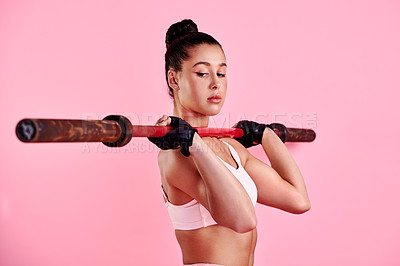 Buy stock photo Studio shot of a sporty young woman exercising with a barbell against a pink background