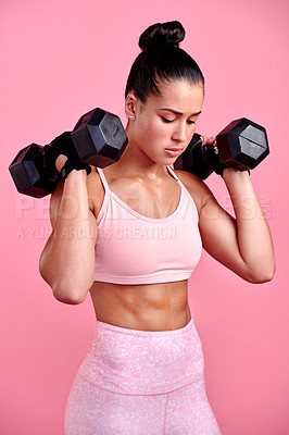Buy stock photo Studio shot of a sporty young woman exercising with dumbbells against a pink background