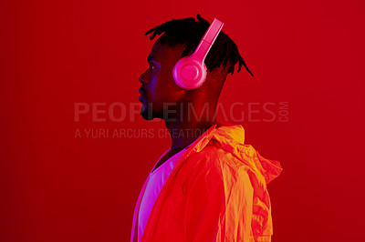 Buy stock photo Red filtered shot of a young sportsman wearing headphones while posing in the studio