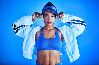 Buy stock photo Cropped portrait of an attractive young female athlete posing against a blue background