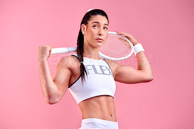 Buy stock photo Studio shot of a sporty young woman holding a tennis racket against a pink background