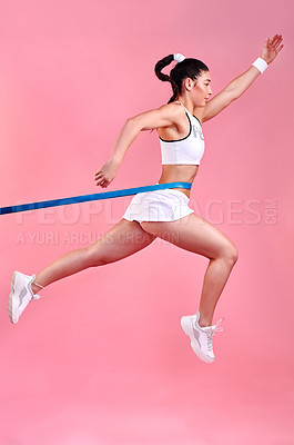 Buy stock photo Studio shot of a sporty young woman jumping with a band around her waist against a pink background