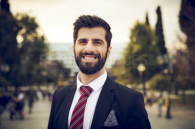 Buy stock photo Cropped portrait of a handsome young businessman smiling while standing outdoors in a foreign city