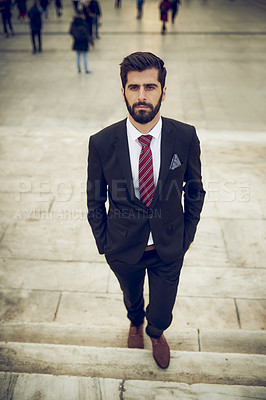 Buy stock photo High angle shot of a handsome young businessman going up a staircase outdoors in a foreign city