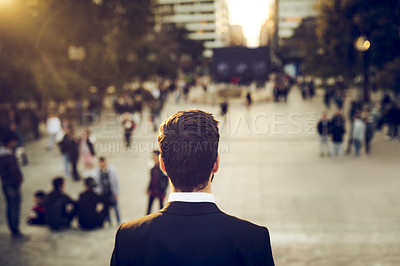 Buy stock photo Rearview shot of an unrecognizable businessman standing outdoors in a foreign city