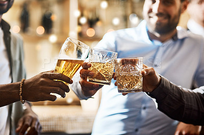 Buy stock photo Cropped shot of a group of cheerful young friends having a celebratory toast with their drinks inside of a bar at night