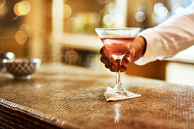 Buy stock photo Cropped shot of an unrecognizable barman serving a drink on the bar counter inside of an establishment at night