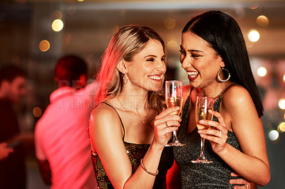 Buy stock photo Cropped shot of two cheerful young women having a celebratory toast with drinks inside of a bar at night