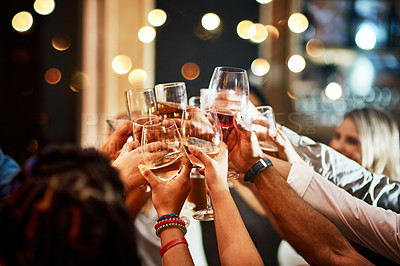 Buy stock photo Cropped shot of a group of unrecognizable friends having a celebratory toast with their drinks inside of a bar at night