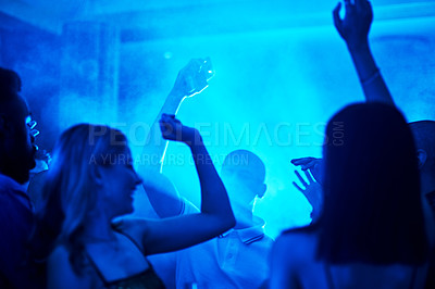 Buy stock photo Cropped shot of a crowd of people dancing inside of a club at night