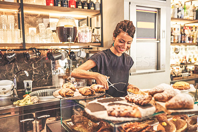 Buy stock photo Cropped shot of a cheerful young woman placing baked goods onto a tray inside of a cafe during the day