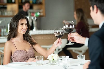 Buy stock photo Shot of a happy young couple toasting with wine on a romantic date at a restaurant