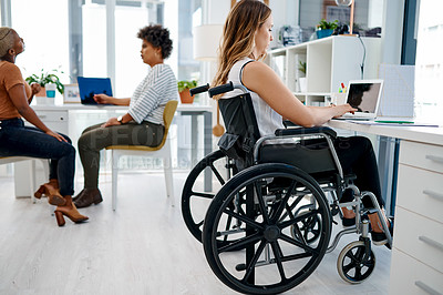 Buy stock photo Shot of a businesswoman sitting in her wheelchair while working at her desk