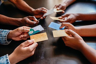 Buy stock photo Closeup of a group of unrecognizable people holding out their credit cards over a table