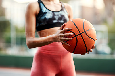 Buy stock photo Cropped shot of an unrecognizable sportswoman standing on the court alone and holding a basketball during the day