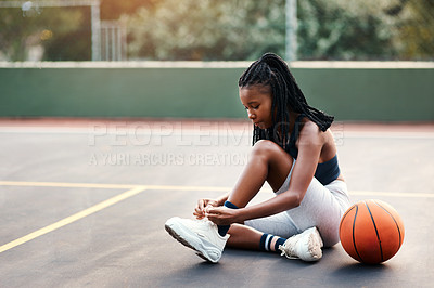 Buy stock photo Cropped shot of an attractive young sportswoman sitting on the court and tying her shoelaces before playing basketball