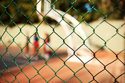 Buy stock photo Cropped shot of an unrecognizable group of people standing behind the fence of a basketball court during the day