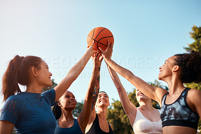 Buy stock photo Cropped shot of a diverse group of sportswomen holding a basketball together before playing a game during the day