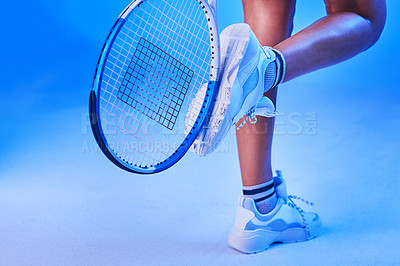 Buy stock photo Rearview shot of an unrecognizable young female tennis player posing against a blue background