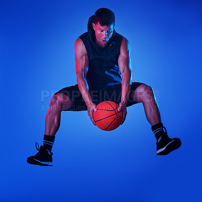 Buy stock photo Blue filtered shot of a sportsman playing basketball in the studio
