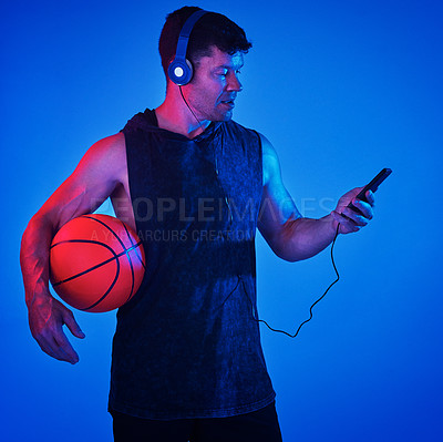 Buy stock photo Blue filtered shot of a sportsman wearing headphones while holding a basketball