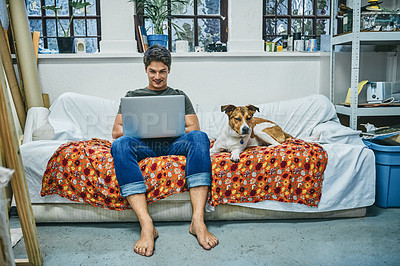 Buy stock photo Shot of a young man using a laptop while relaxing with his dog on a sofa at home
