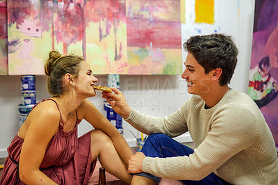 Buy stock photo Shot of a cheerful young couple feeding each other pizza while having a date surrounded by candles and paintings inside of an art studio