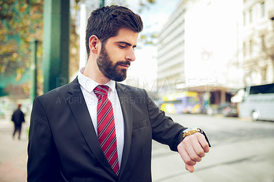 Buy stock photo Shot of a young businessman checking his watch in the city