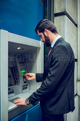 Buy stock photo Shot of a young businessman making a transaction at an ATM