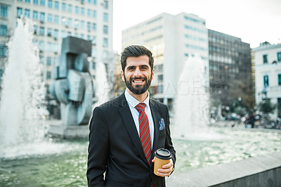 Buy stock photo Portrait of a young businessman holding a cup of coffee while out in the city