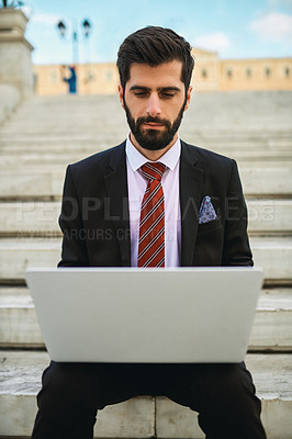 Buy stock photo Shot of a young businessman using a laptop while sitting on a staircase in the city