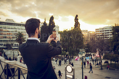 Buy stock photo Cropped shot of a handsome young businessman taking a selfie while standing on a balcony in a foreign city