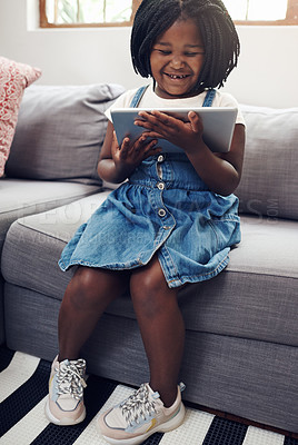 Buy stock photo Full length shot of an adorable little girl using a digital tablet while sitting on a sofa at home