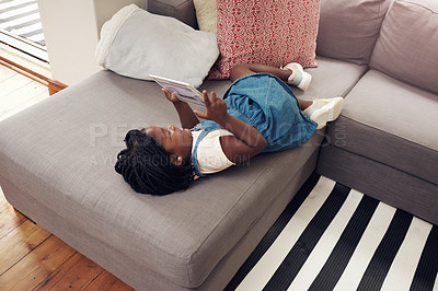 Buy stock photo Full length shot of an adorable little girl using a digital tablet while lying down on a sofa at home