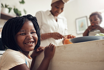 Buy stock photo Portrait of an adorable little girl standing in the kitchen while her mother and baby sister in the background