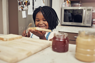 Buy stock photo Cropped shot of an adorable little girl making lunch for herself in the kitchen at home