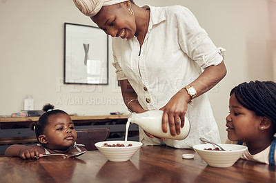 Buy stock photo Cropped shot of a young mother preparing cereal for her two adorable young daughters at home