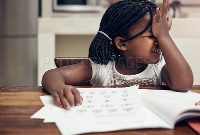 Buy stock photo Cropped shot of an adorable little girl thinking hard while doing her homework at home