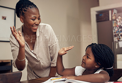 Buy stock photo Cropped shot of a young mother and daughter joining hands for a high five while doing homework together at home