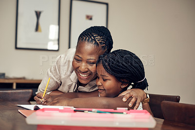 Buy stock photo Cropped shot of a mother helping her young daughter with her homework at home