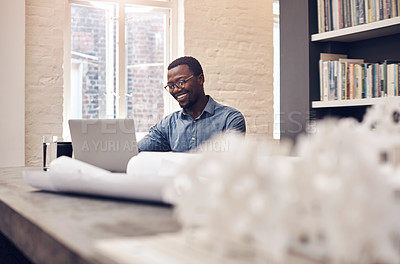 Buy stock photo Cropped shot of a handsome young male architect smiling while working on a laptop in a modern office